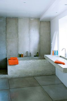 Industrial feel in this concrete filled bathroom. Orange adds much needed warmth.