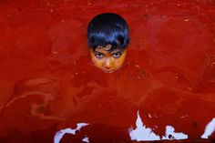 An Indian boy plays in a pool of colored water, at the end of Holi celebrations, the Hindu festival of colors at the Baldev Temple in Dauji, 180 kilometers (113 miles) south of New Delhi, India, on March 18 - Rajesh Kumar Singh / Associated Press