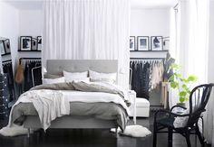 Moderni makuuhuone, jossa iso valko-harmaa sänky keskellä musta-valkoista huonetta. Sängyn takana olevan valkoisen verhon takana on säilytystilaa vaatteille.