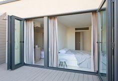 La sequenza di enormi finestrature collega la casa del team CaSA ai 100 mq di terrazzo dotato anche di una doccia esterna per la calura estiva. La prima parte dello spazio esterno, chiuso da un tramezzo, ospita una zona lavanderia per lavare e asciugare i vestiti lontano dalla vista