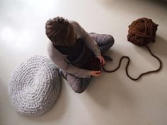 make a mega-crochet pouf  -  this instructable is FANTASTIC.  not only does the author give you the pattern for free, she also teaches you how to make your own giant yarn out of smaller yarn so you don't have to spend an arm and a leg on giant wool