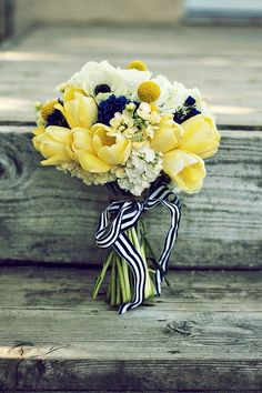 This bouquet is the perfect mixture of ivory, yellow, and navy blue. The soft yellow tulips and striped ribbon is what makes it perfect for a navy blue and yellow wedding.