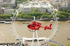An aerial photograph of the London Eye, with a London Air Ambulance helicopter flying in the foreground
