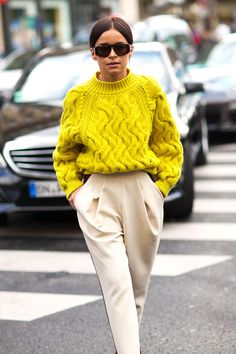 bright yellow, oversized, cabled sweater and pleated tan in Paris.