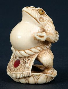 An ivory netsuke, late 19th-early 20th century, signed Tomomatsu. A very finely carved Sumo wrestler toad. He stands on a lotus leaf in typical pose wearing his apron fundoshi with inlaid tortoiseshell. Double inlaid eyes, the whole piece has a nice evenly worn patina. Height 4.7 cm