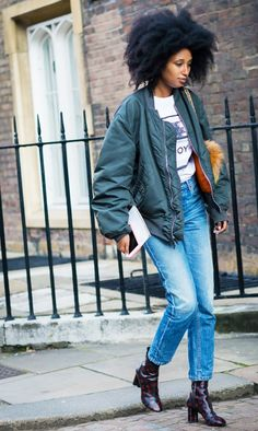 Julia Sarr Jamois wears a graphic t-shirt, bomber jacket, high-waisted jeans, and Louis Vuitton boots