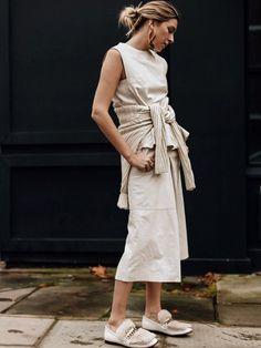 ロンドン在住のパリジェンヌ、カミーユが魅せる、エクリュカラーのワントーンスタイル。「マックキュー アレキサンダー・マックイーン」のレザー素材のセットアップは、ミディ丈のパンツで軽やかさをアップ。ニッ...