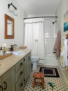 Boys bathroom in a traditional style with white and black penny tile on the floor and white subway tile in the shower.