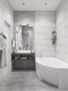 This beautiful grey bathroom has a space-saving corner bath and a contemporary counter top basin.