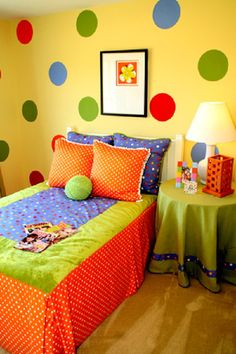 I like how the bed looks very neat and comfortable. The colors are red-orange, blue, and green.