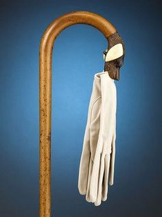 """Canine Glove Holder Cane - This loyal canine on the crook handle of this cane will be happy to hold your gloves. A press of the lever under its jaw opens the dog's mouth. Ivory ears and glass eyes accentuate this handsomely carved pup. 31 1/4"""" length"""