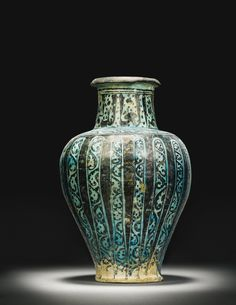 A Raqqa baluster-form pottery jar, Syria, first half 13th century of inverted pear-shaped form on a spreading foot with recessed base, the high sloping shoulders rising to a straight cylindrical neck with everted mouth, the body decorated in black under a turquoise glaze with bands containing foliate scrolls, the neck with a band of calligraphy in Thuluth script, old inventory number printed on base: 30.26. 34cm. height.