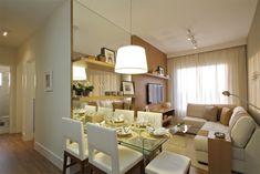 Na parede do living e sala de jantar, foi utilizado um painel em madeira e revestimento em espelho. A madeira ficou locada na parte do living, dando uma sensação mais acolhedora e aconchegante. Já o espelho, ficou locado na parede onde está a mesa de jantar, parecendo ampliar o ambiente. A prateleira em madeira liga ambos materiais, criando a mesma linguagem para essa área do decorado http://ow.ly/e45A0
