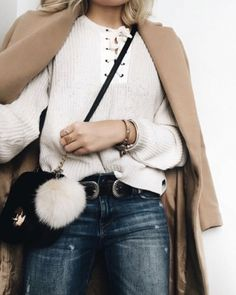 A lace-up sweater layered with a camel coat, destroyed jeans, and a crossbody bag.