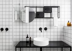 Мебель в ванной главной спальне повторяет сетчатую структуру стеллажа в жилой комнате, только окрашена в контрастный черный цвет. .