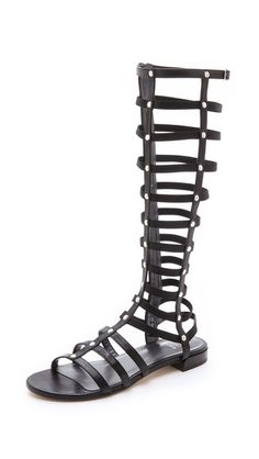 Gladiator Sandals - Black Tonal elastic straps lend a comfortable, contoured fit to these sexy knee high gladiator sandals. Soft leather bands offer easy structure, and a buckle strap adjusts the top. Exposed zip closure. Leather sole. Leather: Goatskin. Made in Spain. This item c Trovato su Styletorch