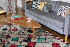 Aloha ! table basse en bois clair Sengtai, canapé gris, coussins colorés dépareillés, tapis berbère