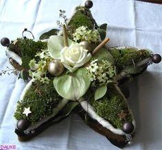 kerst bloemstuk, een ster van mos versierd met kerstballen en bloemen (roos anthurium)