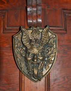 Sculpted Krampus head adorned with mistletoe and holly,    cast in resin and hand painted 8.5 tall, brass hanger on back