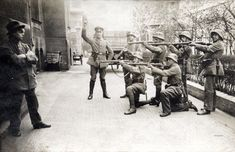 "The original caption describes the scene as an execution of a communist in Munich in 1919. This photo though appears posed: the ""victim"" is standing against a wall and the ""firing squad"" is about to shoot their rifles from five paces away. Any such action would have resulted in serious injury or death for the shooters as well because of ricochets."