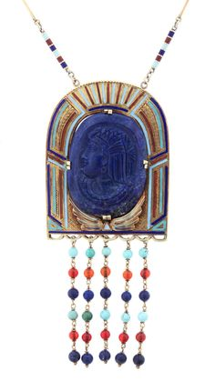 """Egyptian Revival Necklace. Egyptian Revival necklace, circa 1925, is a beautiful composition in 14K gold, lapis and enamel, the 1-1/2"""" x 2"""" arched pendant set at center with a carved oval lapis profile, surrounded by multi-colored enamel and engraved gold decorative plaque, with beaded tassels of turquoise, lapis, and carnelian beads. The 30"""" 14K gold chain alternates flat and twisted gold links with multi-colored enamel cylindrical spacers."""