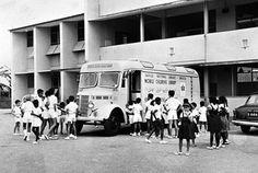 Mobile Children's Library van    A black and white photograph of the mobile children's library parked in a school compound with children waiting to get in.