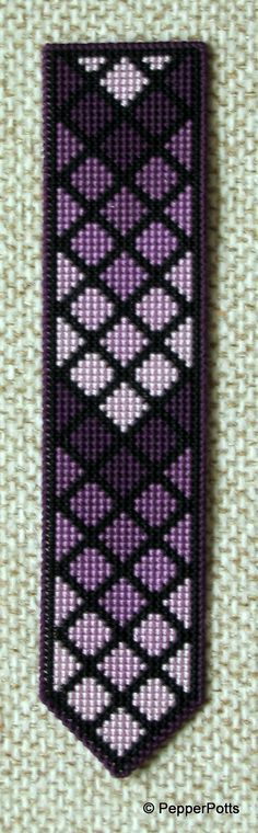 Worked on 14ct plastic canvas in a cross stitch, using various shades of purple stranded cotton leftovers. The diamonds were worked first, then the contrasting lines filled in in a very deep purple stranded cotton. It is backed with thin craft foam using a double sided adhesive film.