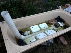 Wicking garden bed made from a bath and upturned pots, offcuts etc