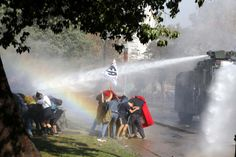 Student demonstrators take cover from a jet of water released from a riot police vehicle during a demonstration to demand changes in the Chilean education system, in Santiago May 8, 2014.
