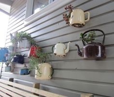 """outdoor tea kettles-I am hanging them on a small portion of hurricane fence using metal shower hooks-no plants just for """"whimsey"""""""