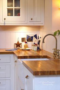 white kitchen, wooden counter top, interesting treatment to back-splash...