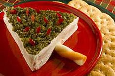 This Cheesy Christmas Tree is so cute, you won't believe how easy it is to make! Cut a block of cream cheese in half diagonally, then push the triangles together to form the tree. Spread pesto and red pepper slices over the top, cut a piece of string cheese for the trunk, and ta-da: a delicious holiday snack to serve with RITZ crackers!