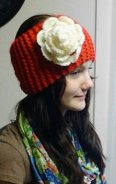Red knit ear warmer with cream colored rose done by Jodi Villanella.