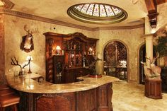 Peruvian travertine columns were carried into this space.  Note the detail in the bar, with an expansive travertine counter top.  The free floating ceiling accented with stained glass dome draws your eye up.