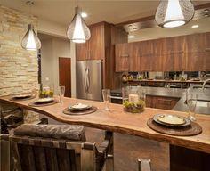 Mientras está conectado a una pared divisoria de pie, todavía nos tienen a esta creación única como una isla de cocina.  Una gran losa única de la madera natural tallada hace que para el espacio abundante de comida en la cocina, al tiempo que ayuda a definir la cocina de madera natural en sí.