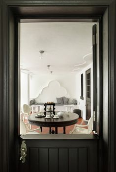 New Cape Dutch House eclectic dining room.  Gable shape in stucco at breakfast booth and sculpted stucco ceiling details.  Dutch door.
