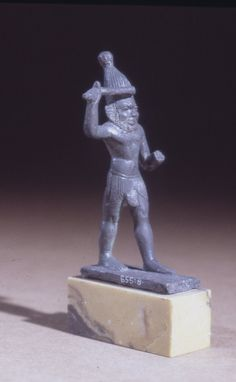 Bronze figure of Bes wearing the mu-headdress and holding a club aloft; tang beneath the plinth. Height: 9.7 cm .I British Museum