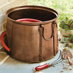Keep your hose handy, but out of sight, with our decorative Aged Copper Hose Pot. Sturdily handmade of iron with rustproof, aged copper finish and heavy-duty bail handles for easy carrying. The footed base has holes to allow for drainage.