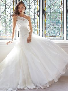 Silky organza spans the fit and flare silhouette of Sophia Tolli Y21440 Sissy Wedding Dress, accented with a crystal-beaded one-shoulder strap and a side brooch. The asymmetrical neckline leads the ruched bodice, which tapers into the drop waist.