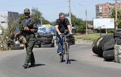 civilian bike usage in Ukraine: An armed pro-Russian separatist (L) stands guard at a check point
