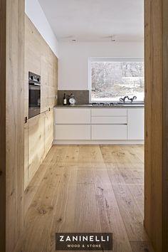 Cucina moderna in legno e pietra. Ante in laccato bianco sotto il piano di lavoro grigio, crea un bellissimo contrasto con il pavimento e le colonne in Rovere.  #cucina #legno #pietra #design #interni #arredamento #casa