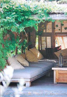 soffor längs sida/sidorna på väggen med kuddar och bord. växter