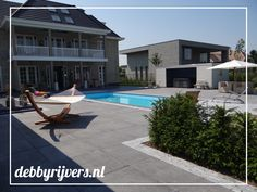 Luxe moderne strakke villatuin met zwembad, hardstenen bestrating en een jacuzzi.   Luxury modern clean gardendesign including swimmingpool, Blue stone pavement and a jacuzzi.