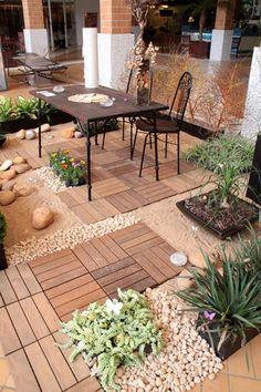 Mesa e cadeiras no jardim. O projeto de Adele Heusi e Ana Maria Rufato possui samabaias e zâmias entre o caminho de madeira e seixos que leva até a mesa e as cadeiras de ferro