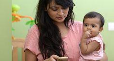 Mãe solteira consulta o telefone com a filha no colo
