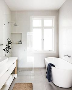Minimalist bathroom with a standing tub and glass shower // light and airy bathroom, natural light, clean neutral colors, bathroom inspiration