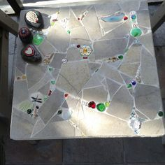 Mosaic end table with a couple of mosaic rocks on top. This is from left over floor tile and little extra fun things for interest. Katie Waller