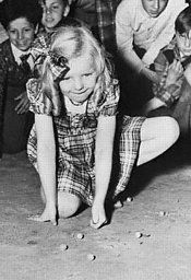 Little girl playing marbles - how many of you out there remember doing this? I loved playing marbles