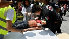 A woman is assisted after being injured during a quake in Mexico City on September 19, 2017. A powerful earthquake shook Mexico City on Tuesday, causing panic among the megalopolis' 20 million inhabitants on the 32nd anniversary of a devastating 1985 quake. The US Geological Survey put the quake's magnitude at 7.1 while Mexico's Seismological Institute said it measured 6.8 on its scale. The institute said the quake's epicenter was seven kilometers west of Chiautla de Tapia, in the…
