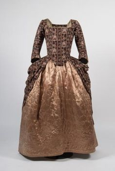 Open gown and petticoat, c.1770-1780. The hand block printed cotton was known as 'dark ground chintz'. The bodice fastens with pins and the skirt is arranged à la Polonaise by means of a series of tied tapes inside. Worn with quilted satin petticoat and a fine linen handkerchief.